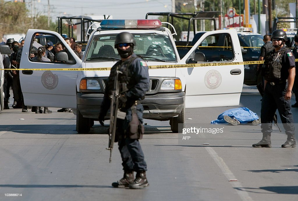 Members of the Federal Police secure the street as the body of a municipal police officer lies dead in Ciudad Juarez Mexico on September 7 2010 A...