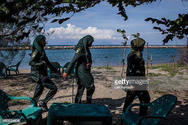 Members of the female sharia police known as Wilayatul Hisbah walk in beach as they patrol on December 12 2014 in Banda Aceh Indonesia Aceh is the...