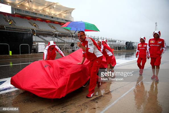 Members of the Ferrari team push a car down the pit lane as heavy rain falls before final practice for the United States Formula One Grand Prix at...