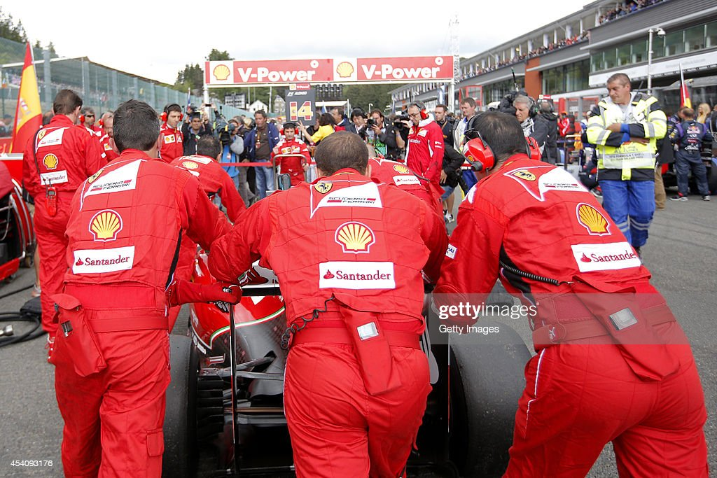 Members of the Ferrari team push one of the cars on to the grid before the Belgian Grand Prix at Circuit de Spa-Francorchamps at Circuit de Spa-Francorchamps on August 24, 2014 in Spa, Belgium.
