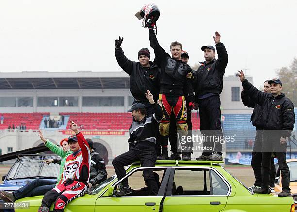 Members of the Filmka Stunt Team based in Hollywood wave to audience after performing car stunts during a stunt show December 9 2006 in Wuhan of...