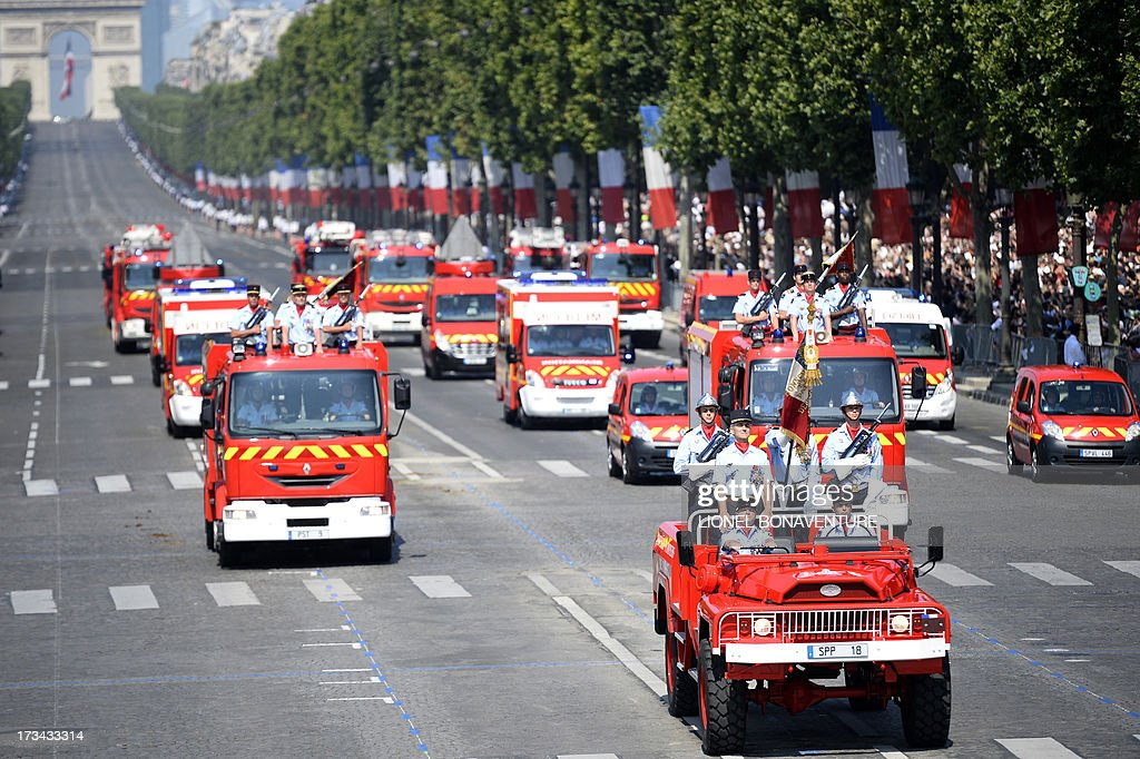 Members of the fire brigade drive during the Bastille Day parade on the Champs-Elysees avenue, on July 14, 2013 in Paris. AFP PHOTO / LIONEL BONAVENTURE