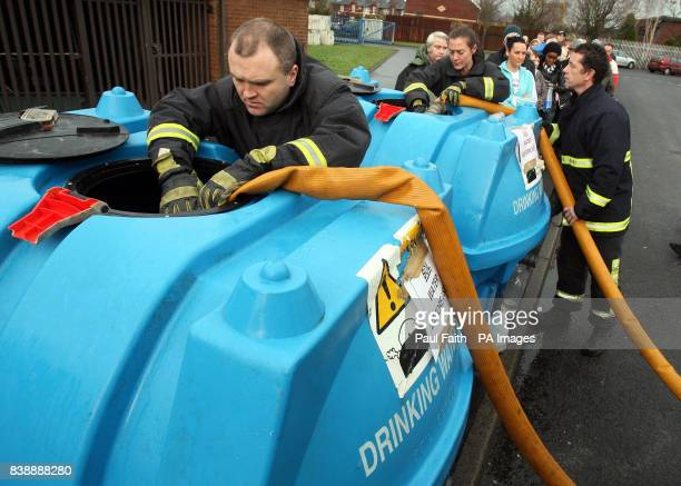 Members of the fire service fill up tanks of drinking water as people wait in line at Avoniel leisure centre in east Belfast with empty bottles as...