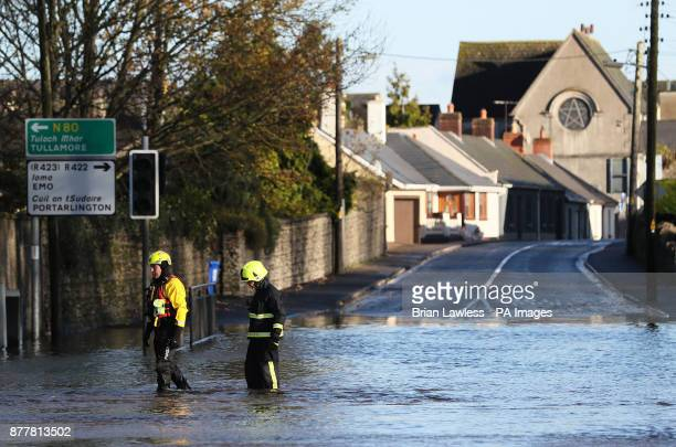 Members of the fire service walk through flood water in Mountmellick Co Laois after three rivers burst their banks and flooded dozens of homes