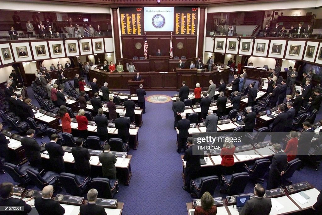 Members of the Florida House bow their heads in prayer at the opening of the historic special session of the Florida State Legislature to elect their...