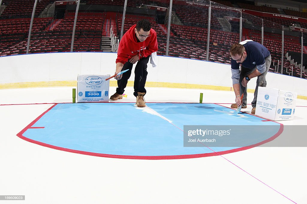Members of the Florida Panthers crew prepare the ice surface by painting the lines and logos at the BB&T Center on January 14, 2013 in Sunrise, Florida.