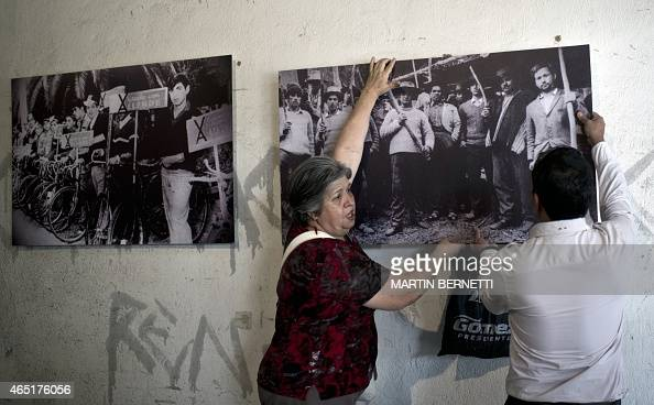 Members of the 'Former Political Prisoners of the National Stadium' human rights association arrange some photographs in a now gallery that once...
