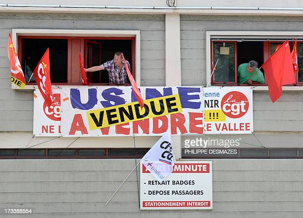 Members of the French CGT union stand in a window with CGT flags and banner which reads 'Factory on sale' and 'Factory sold' at the Rio Tinto Alcan...