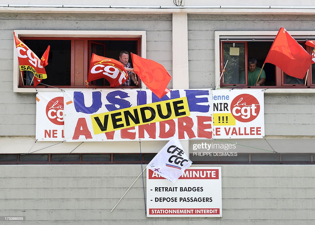Members of the French CGT union stand in a window with CGT flags and banner which reads 'Factory on sale' and 'Factory sold' at the Rio Tinto Alcan (RTA) aluminum factory in Saint-Jean-de-Maurienne, southeast of France, on July 13, 2013 prior to the visit of French Prime minister Jean-Marc Ayrault and French Minister for Industrial Renewal and Food Industry Arnaud Montebourg. Heads of Rio Tinto Alcan and Germany's Trimet met today in Paris regarding the take over of RTA by Trimet which could save 510 jobs at the two sites of Saint-Jean-de-Maurienne and Castelsarrasin.