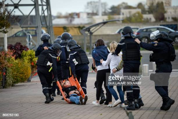 Members of the French Departmental Service of Fire and Rescue framed by French Police officers evacuate victims and a wounded woman on a stretcher...