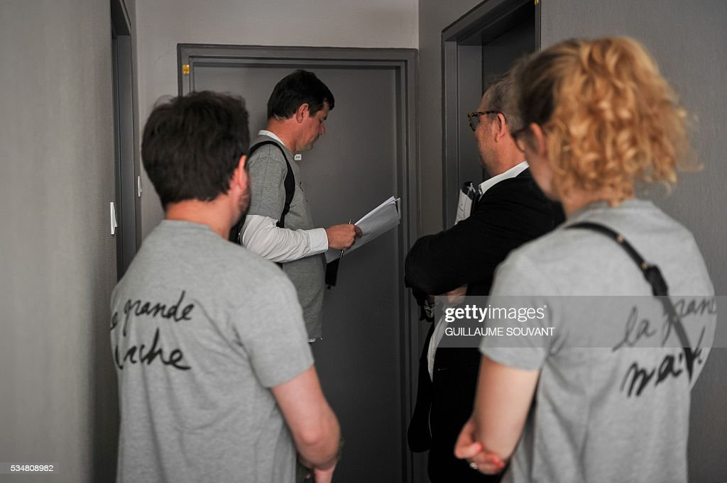 Members of the French Economy minister Emmanuel Macron's political movement 'En Marche' (On the Move) wait in front of a door during a door-to-door campaign on May 28, 2016 in Tours, central France. Militants wear a tee-shirt reading 'En Marche' (On the Move). SOUVANT