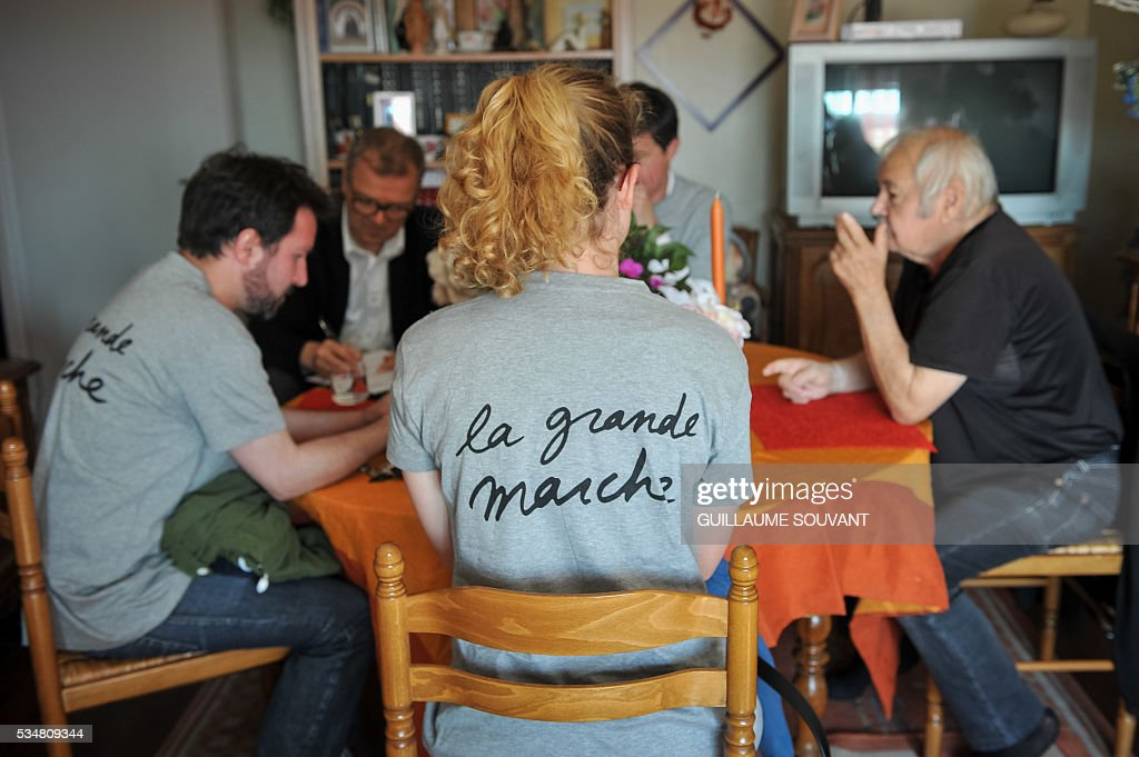 Members of the French Economy minister Emmanuel Macron's political movement 'En Marche' (On the Move) speak to a man at his home during a door-to-door campaign on May 28, 2016 in Tours, central France. Militants wear a tee-shirt reading on the back 'The great march'. SOUVANT