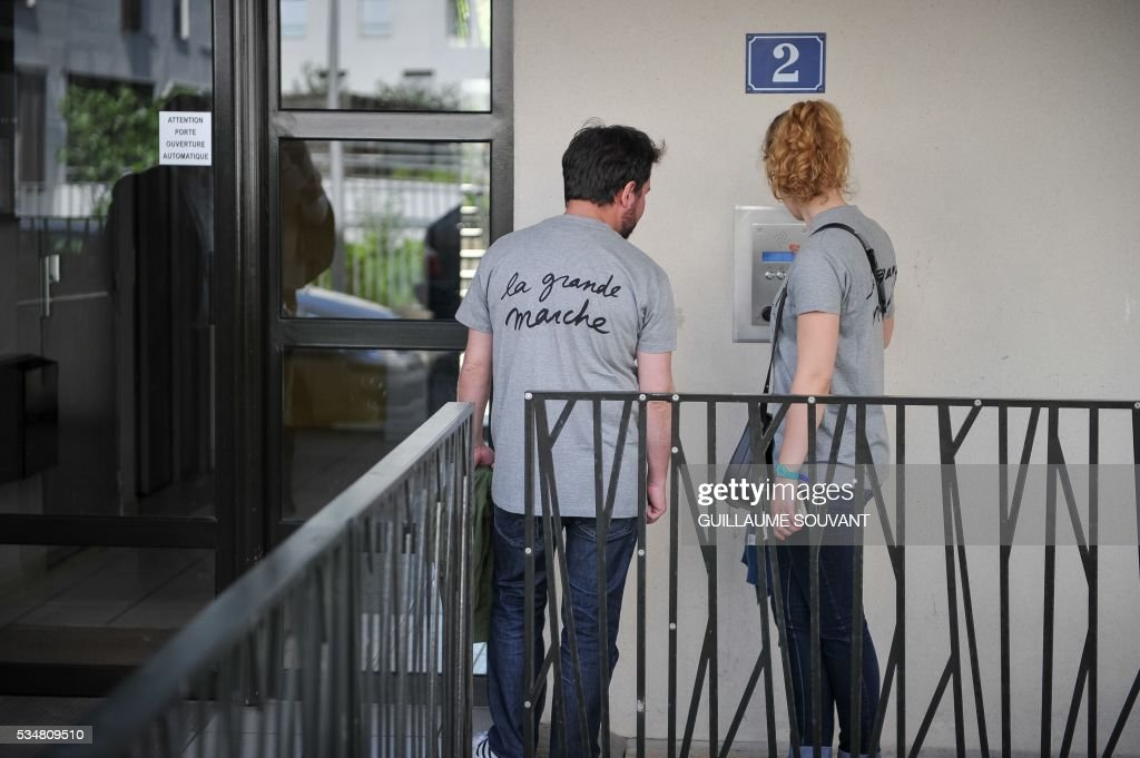 Members of the French Economy minister Emmanuel Macron's political movement 'En Marche' (On the Move) wait in front of a door during a door-to-door campaign on May 28, 2016 in Tours, central France. Militants wear a tee-shirt reading on the back 'The great march'. SOUVANT