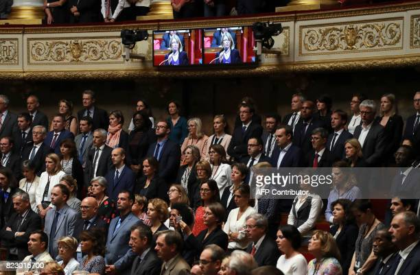 Members of the French National Assembly stand as a photo of late French lawmaker Corinne Erhel is shown on screens and a eulogy is read in her honour...