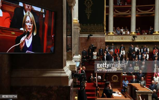 Members of the French National Assembly stand as a photo of late French lawmaker Corinne Erhel is shown on a screen and a eulogy is read in her...
