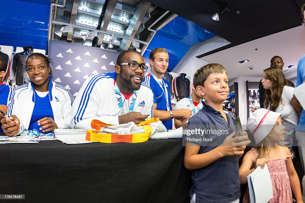 Members of the French National Judo Team, Gevrise Emane, Teddy Riner and Ugo Legrand pose with young fans during a signing session at Adidas Performance Store Champs-Elysees on September 4, 2013 in Paris, France.