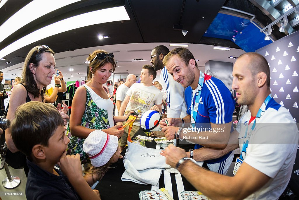 Members of the French National Judo Team Teddy Riner, Ugo Legrand and Alain Schmitt sign autographs to young fans during a signing session at Adidas Performance Store Champs-Elysees on September 4, 2013 in Paris, France.