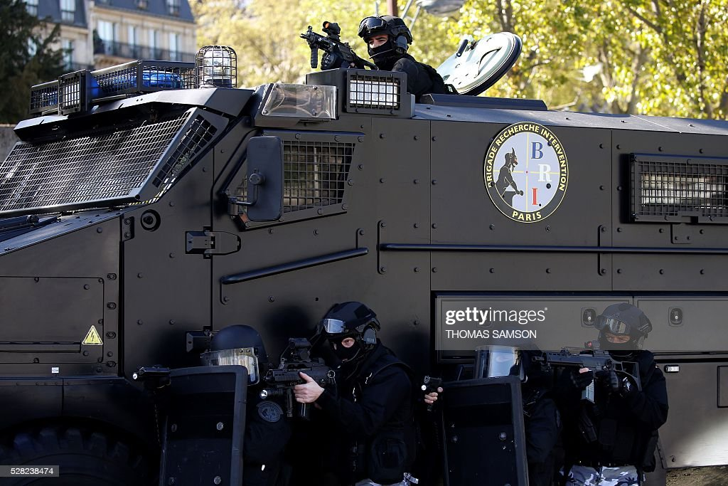 Members of the French national police elite research intervention group (BRI, Brigades de Recherche et d'Intervention) hold their shield as they take part in an exhibition with the group's new armored truck named 'Titus' (Tactical Infantry Transport and Utility System 6x6) in Paris on May 4, 2016. Titus is manufactured bTitus is manufactured by the French Defense Company Nexter. / AFP / THOMAS