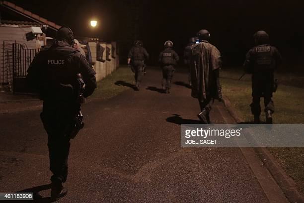 Members of the French police intervention forces walk as they carry out searches in Fleury northern France on January 8 2015 as part of an...