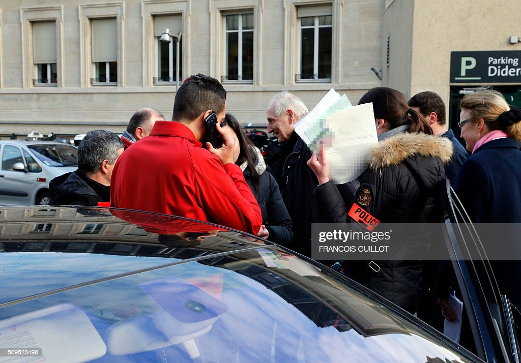 Members of the French police service known as 'Boers', in charge of detecting fake taxis, check a driver's papers at Gare de Lyon station in Paris on February 11, 2016. / AFP / FRANCOIS GUILLOT