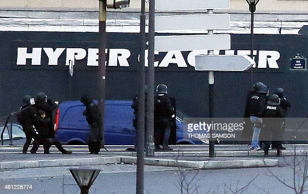 Members of the French police special forces attend to one of their colleagues lying on the ground after they launched the assault at a kosher grocery...