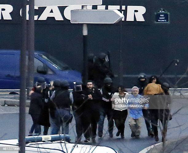 Members of the French police special forces evacuate the hostages after launching the assault at a kosher grocery store in Porte de Vincennes eastern...