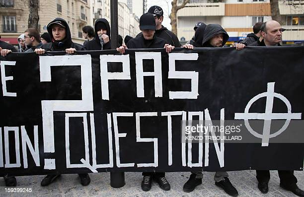 Members of the French student political group GUD hold a banner with the celtic cross nationalist symbol reading 'Marriage adoption No way ' during a...