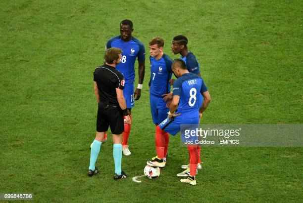 Members of the french team surround match referee Nicola Rizzoli