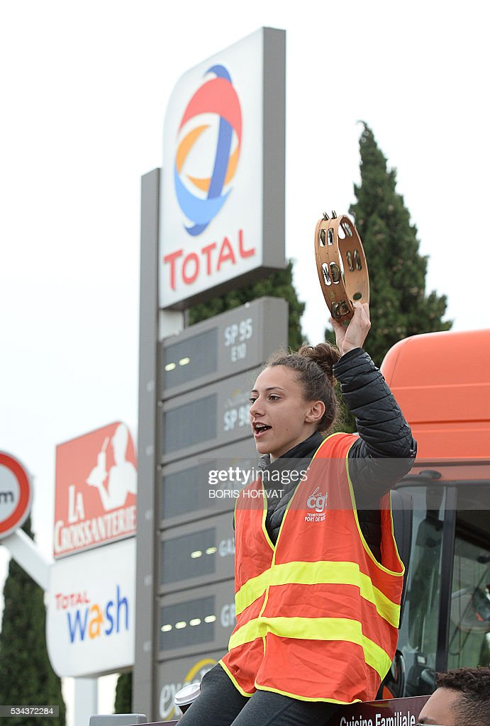 Members of the French union the CGT block the entrance of an industrial zone as they protest against the labour law reforms on May 26, 2016 in Vitrolles in southern France. France faced fresh strikes after nuclear power station workers voted to join gathering protests against labour law reforms that have forced the country to dip into strategic fuel reserves due to refinery blockades. Protesters are furious that the government rammed the labour market reforms through parliament without a vote, which are designed to address France's famously rigid labour market by making it easier to hire and fire workers. / AFP / BORIS