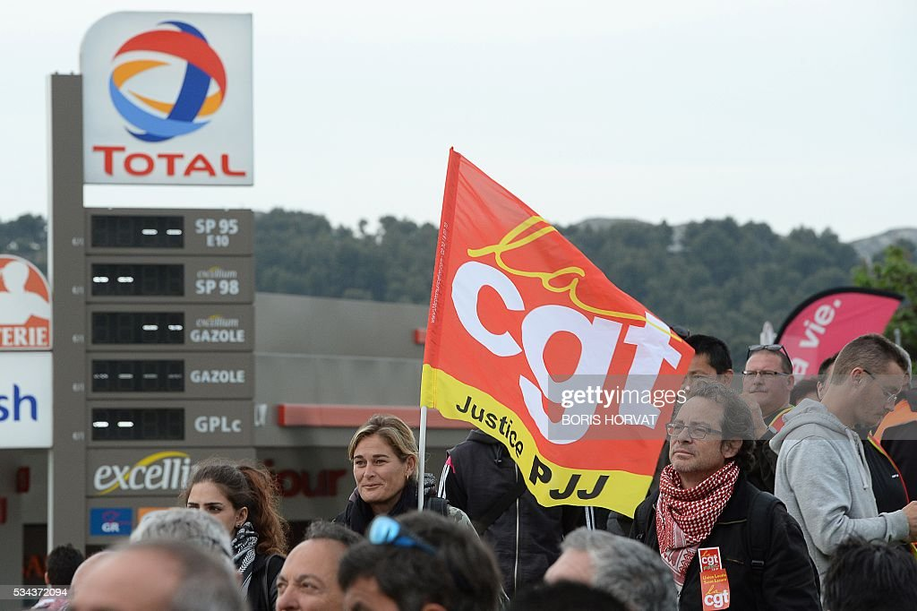 Members of the French union the CGT block the entrance of the industrial zone as they protest against the labour law reforms on May 26, 2016 in Vitrolles in southern France. France faced fresh strikes after nuclear power station workers voted to join gathering protests against labour law reforms that have forced the country to dip into strategic fuel reserves due to refinery blockades. Protesters are furious that the government rammed the labour market reforms through parliament without a vote. / AFP / BORIS