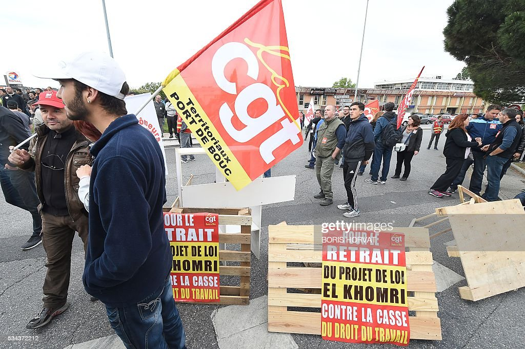 Members of the French union the CGT block the entrance of the industrial zone as they protest against the labour law reforms on May 26, 2016 in Vitrolles in southern France. France faced fresh strikes after nuclear power station workers voted to join gathering protests against labour law reforms that have forced the country to dip into strategic fuel reserves due to refinery blockades. Protesters are furious that the government rammed the labour market reforms through parliament without a vote, which are designed to address France's famously rigid labour market by making it easier to hire and fire workers. / AFP / BORIS