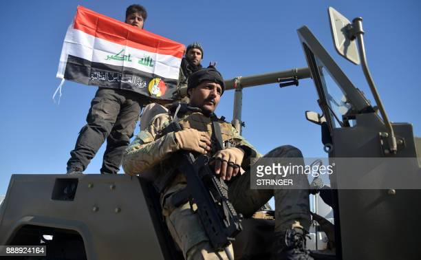 Members of the Furqat alAbbas Brigade of the Hashed alShaabi paramilitaries celebrate with an Iraqi flag defaced with their combat insignia after the...