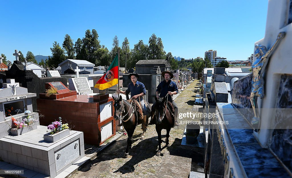 Members of the Gaucho Traditions Center ride on horses along the Municipal cementery to pay homage to their fellow member Silvio Beuren, one of the victims of the blaze in a disco on the eve, at the municipal cementery on January 28, 2013 in Santa Maria, southern Brazil. A massive blaze at a nightclub in Brazil killed more than 230 people and left relatives desperately searching for loved ones as horrific accounts emerged of a tragic rush to escape the inferno. AFP PHOTO/ JEFFERSON BERNARDES