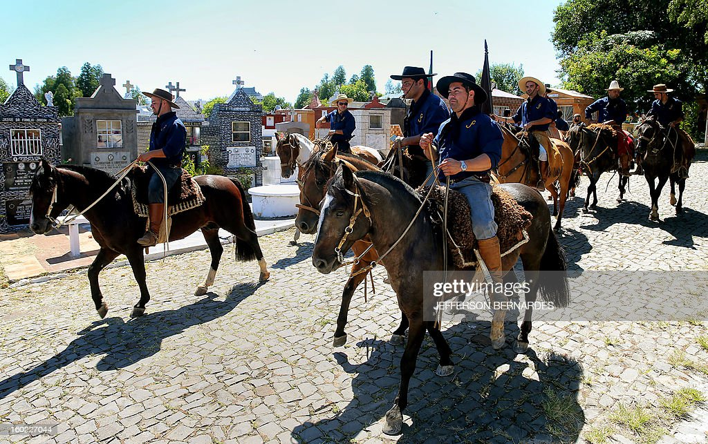 Members of the Gaucho Traditions Center ride on horses along the Municipal cementery to pay homage to their fellow member Silvio Beuren, one of the victims of the blaze in a disco on the eve, at the municipal cementery on January 28, 2013 in Santa Maria, southern Brazil. A massive blaze at a nightclub in Brazil killed more than 230 people and left relatives desperately searching for loved ones as horrific accounts emerged of a tragic rush to escape the inferno.