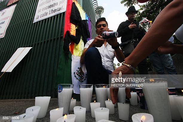 Members of the gay community and others light candles outside the American consulate for a vigil in Guadalajara Mexico on June 12 2016 to mourn the...