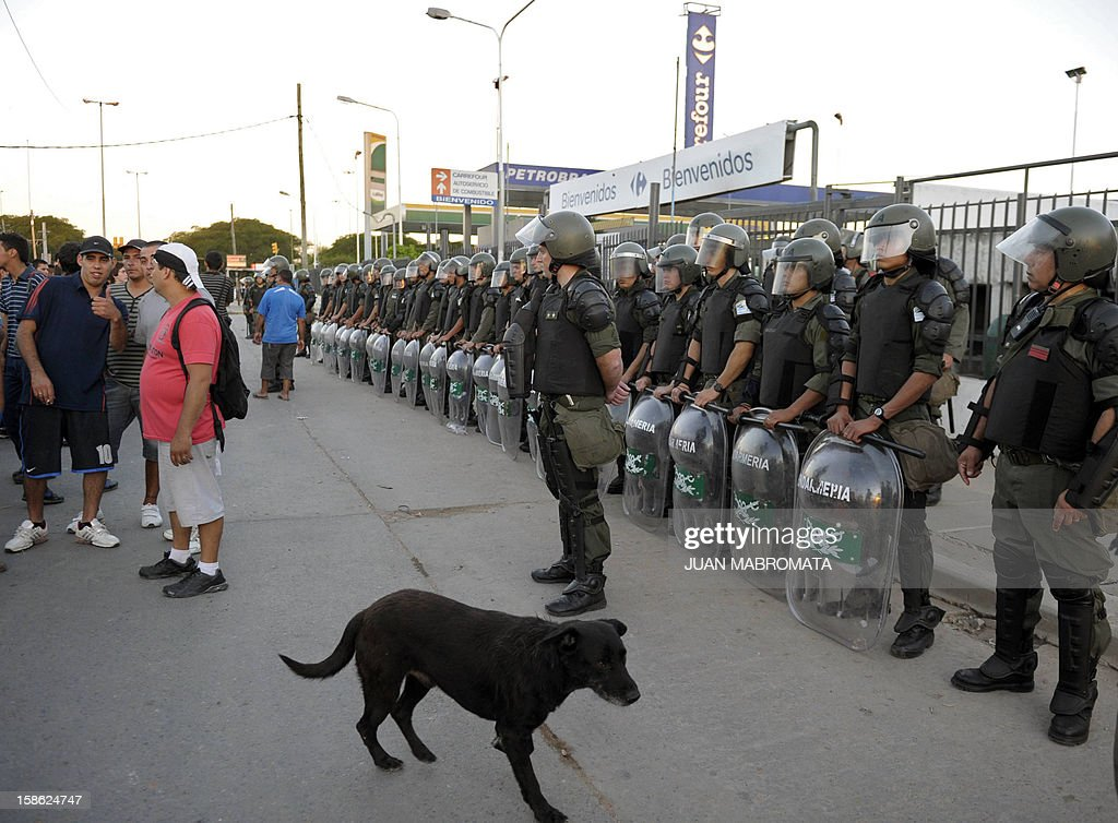 Members of the gendarmerie guard the entrance to a supermarket in San Fernando, Buenos Aires province on December 21, 2012. Two people died Friday and two more were seriously injured as mobs looted supermarkets in Rosario, Argentina's third largest city, an official said. A series of lootings have taken place in five other cities of Argentina since Thursday leaving also near a hundred people injured and 300 detained.