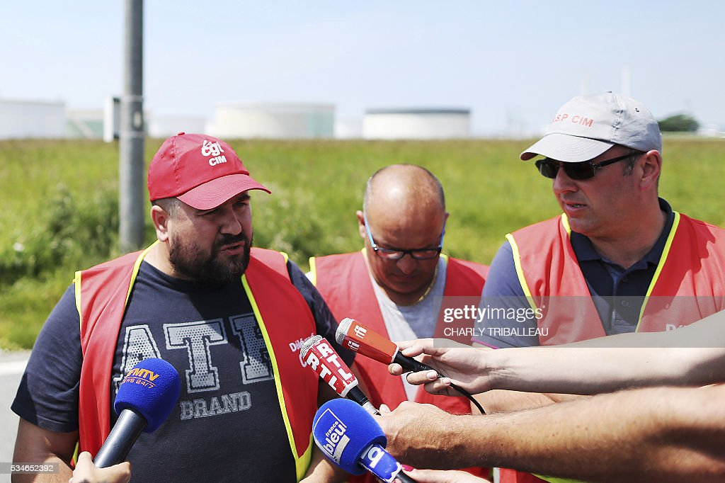 Members of the General Assembly of the CIM (Industrial and Shipping Company): CCE(Central works Councils)'s secretary of the CIM Franck Barbay, CIM's work council secretary Fabian Bourdoulous and Labour union CGT CIM's secretary Mathias Jeanne talk to the press to announce the continuation of the strike of the CIM on May 26, 2016 in Le Havre, northwestern France. French President Francois Hollande vowed on May 27, 2016 to 'stand firm' over a controversial labour law as unions called on workers to step up a wave of industrial action gripping the country.France is battling fuel shortages, transport disruption and violent demonstrations, just as it gears up to host the Euro 2016 football championships in two weeks' time. CROP