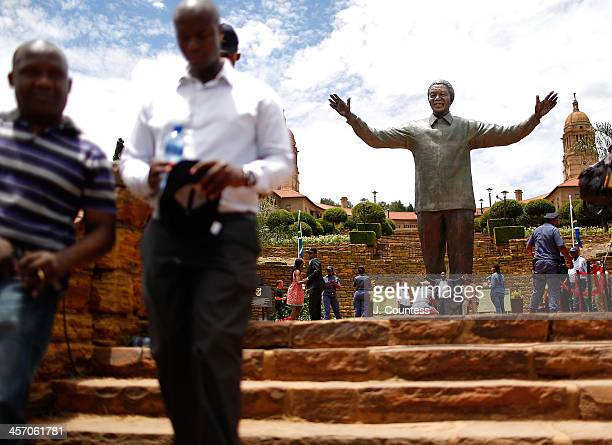 Members of the general public leave the Union buildings after viewing a newly unveiled statue of former South African President Nelson Mandela at the...