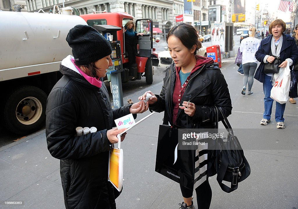 Members of the general public take free samples of di-gel as di-gel helps New Yorkers 'Undo' Black Friday Shopping Troubles on November 23, 2012 in New York City.