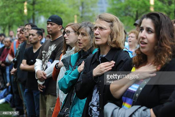 Members of the general public watch a screen projection of US President Barack Obama giving a speech during the dedication ceremony at the National...