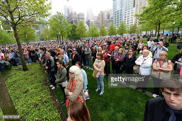 Members of the general public watch a screen projection on the World Trade Center Plaza during the dedication ceremony at the National September 11...
