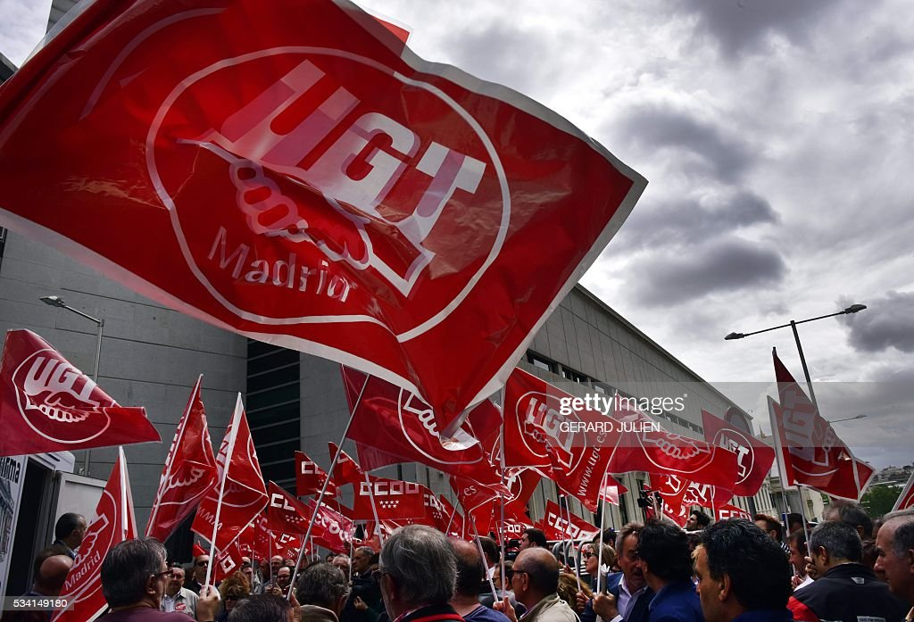 Members of the General Union of Worker (UGT) and the Workers' Commissions (CCOO) hold flags as they bring a massive collection of 700.000 signatures to promote a Popular Legislative Initiative (ILP), outside the Spanish Parliament in Madrid on May 25, 2016. General secretaries of the UGC, Pepe Alvarez, and CCOO, Ignacio Fernandez Toxo, presented today at the Parliament 700.000 signatures to promote the ILP demanding a minimum income of approximately 426 Euros for citizens without resources or in extreme poverty. / AFP / GERARD