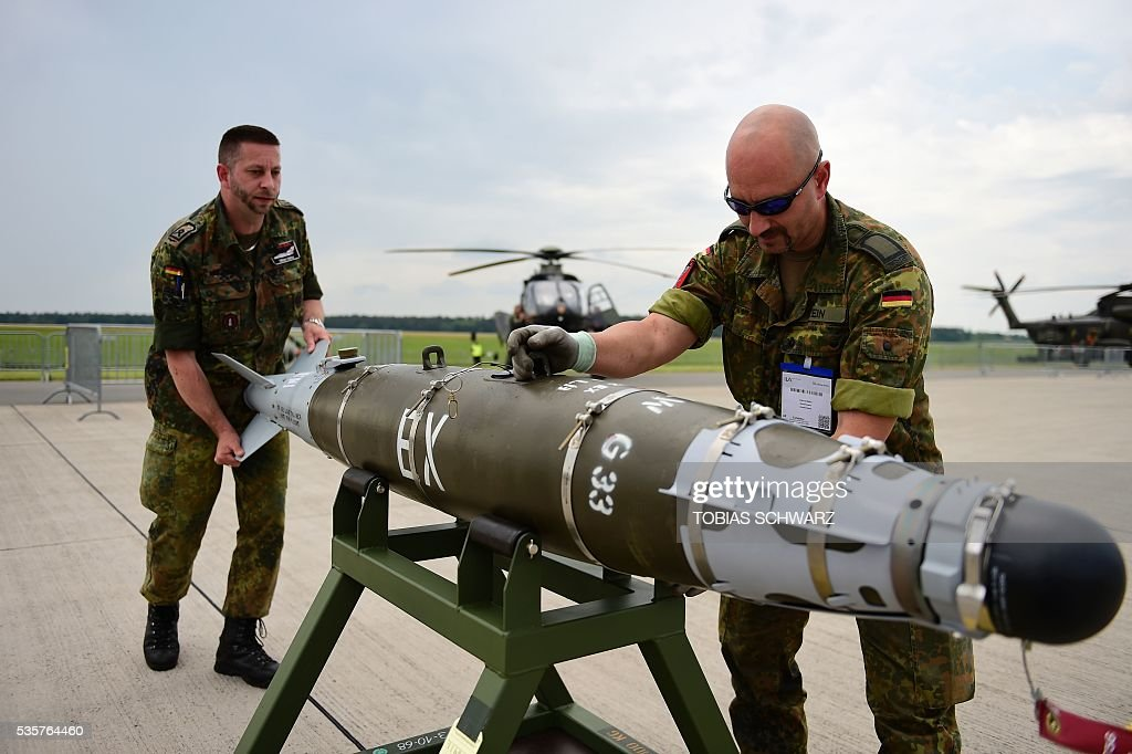 Members of the German Armed Forces Bundeswehr carry a 'GBU 54' weapon system the International Aerospace Exhibition (ILA) in Schoenefeld on May 30, 2016. The Aerospace Exhibition at Schoenefeld Airport near Berlin takes place from June 1 till 4. / AFP / TOBIAS