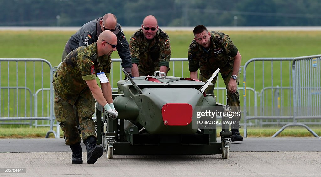 Members of the German Armed Forces Bundeswehr carry a 'Taurus' weapon system the International Aerospace Exhibition (ILA) in Schoenefeld on May 30, 2016. The Aerospace Exhibition at Schoenefeld Airport near Berlin takes place from June 1 till 4. / AFP / TOBIAS