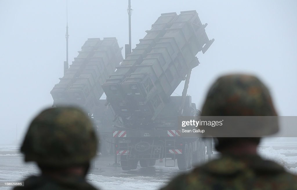 Members of the German Bundeswehr look on as two Patriot missile launching systems stand ready during a press day presentation at the Luftwaffe Warbelow training center on December 18, 2012 in Warbelow, Germany. Germany, along with the USA and the Netherlands, will send two Patriot systems to Turkey in January to protect Turkey from Syrian attacks.