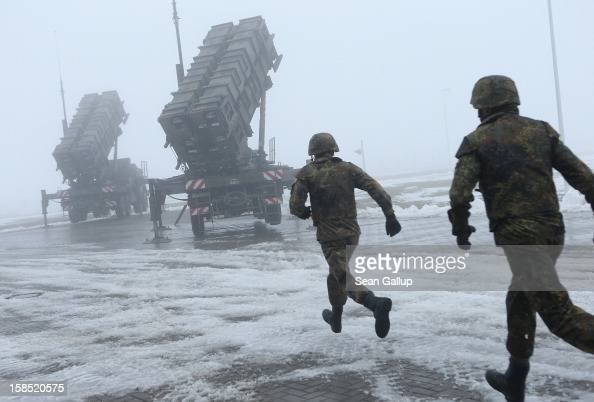 Members of the German Bundeswehr rush toward two Patriot missile launching systems during a press day presentation at the Luftwaffe Warbelow training...