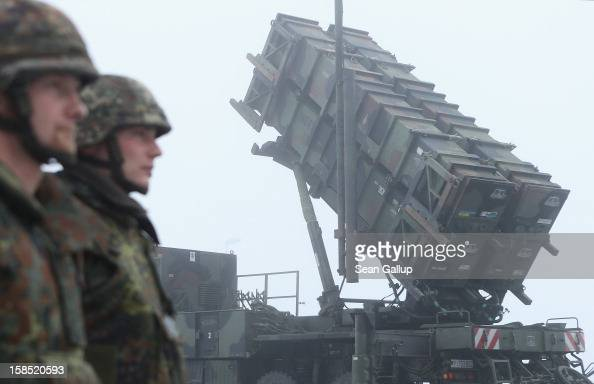 Members of the German Bundeswehr stand at attention next to Patriot missile launching system during a press day presentation at the Luftwaffe...