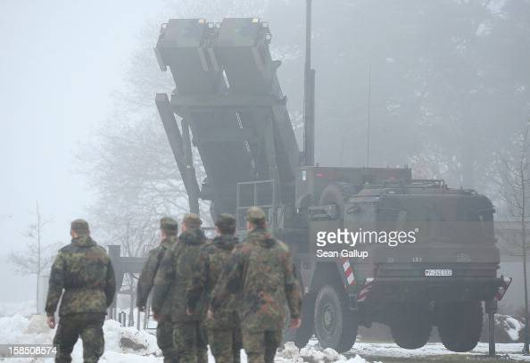 Members of the German Bundeswehr walk past a Patriot launching system during a press day at the Luftwaffe Warbelow training center on December 18...