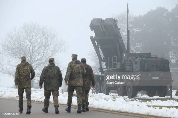 Members of the German Bundeswehr walk past a Patriot missile launching system during a press day at the Luftwaffe Warbelow training center on...