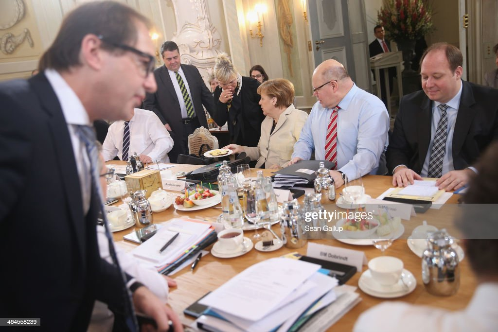 Members of the German government cabinet, including Chancellor <a gi-track='captionPersonalityLinkClicked' href=/galleries/search?phrase=Angela+Merkel&family=editorial&specificpeople=202161 ng-click='$event.stopPropagation()'>Angela Merkel</a> (C), Vice Chancellor and Economy and Energy Minister <a gi-track='captionPersonalityLinkClicked' href=/galleries/search?phrase=Sigmar+Gabriel&family=editorial&specificpeople=543927 ng-click='$event.stopPropagation()'>Sigmar Gabriel</a> (2nd from L), Transport and Digital Technologies Minister <a gi-track='captionPersonalityLinkClicked' href=/galleries/search?phrase=Alexander+Dobrindt&family=editorial&specificpeople=5702301 ng-click='$event.stopPropagation()'>Alexander Dobrindt</a> (L) and Minister of the Chancellery Peter Altmeier (R of Merkel) attend day two of meetings of the German government cabinet at Schloss Meseberg palace on January 23, 2014 in Meseberg, Germany. The government cabinet of Christian Democrats and Social Democrats is on a two-day retreat at Meseberg.